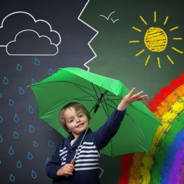 Kid with umbrella with chalk board showing weather in backdrop.
