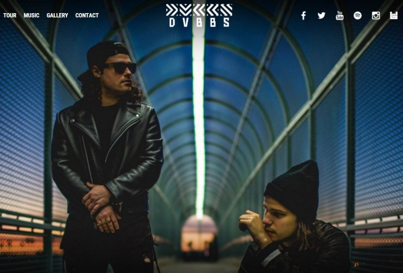 The DVBBS guys close up on a bridge with a backdrop of an evening sky.
